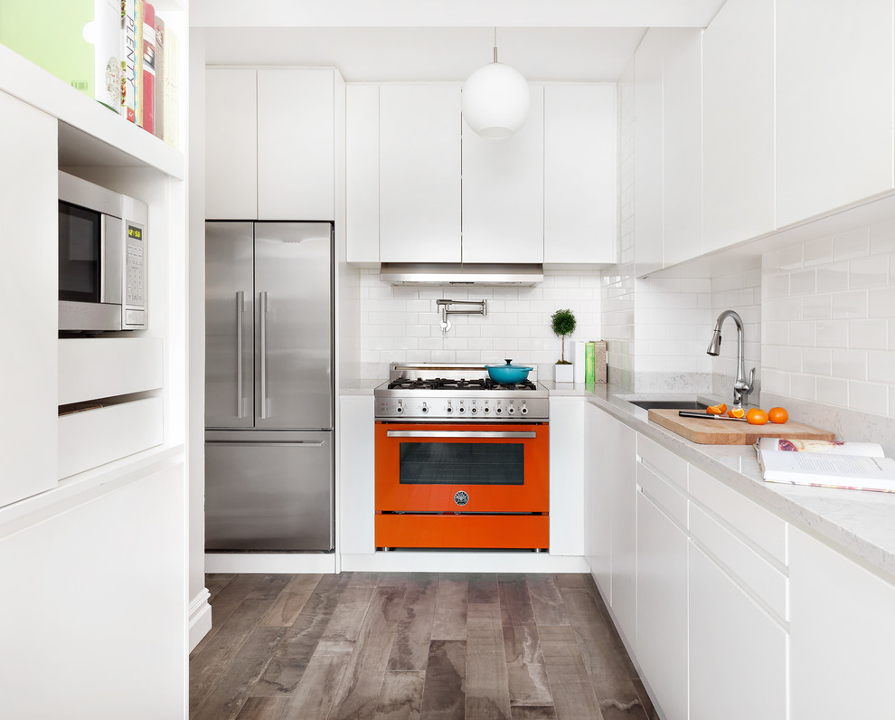Inspiration for a small contemporary l-shaped porcelain tile and gray floor enclosed kitchen remodel in New York with an undermount sink, flat-panel cabinets, white cabinets, subway tile backsplash, colored appliances, no island, white backsplash and white countertops