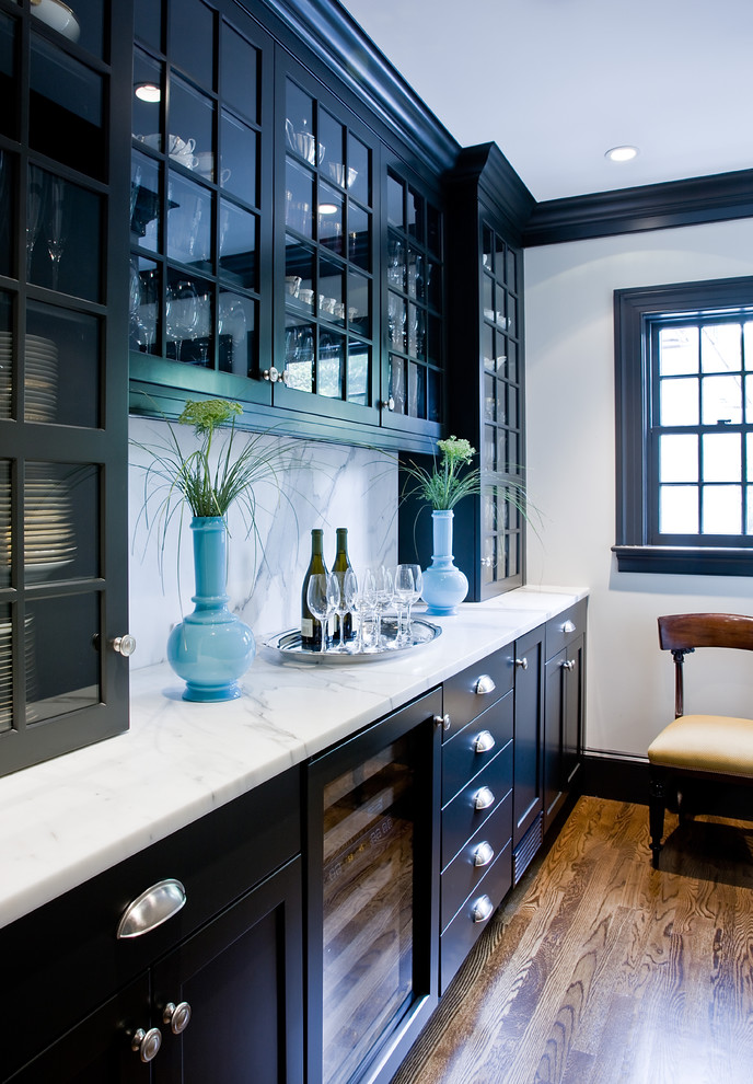 Example of a classic kitchen design in Boston with glass-front cabinets, black cabinets, marble countertops, white backsplash and stone slab backsplash