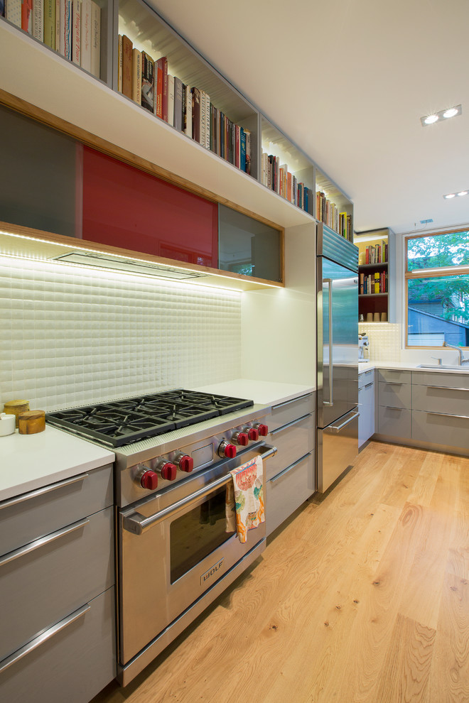 Eat-in kitchen - large contemporary u-shaped light wood floor eat-in kitchen idea in Toronto with a double-bowl sink, flat-panel cabinets, gray cabinets, quartz countertops, white backsplash, porcelain backsplash, stainless steel appliances and a peninsula