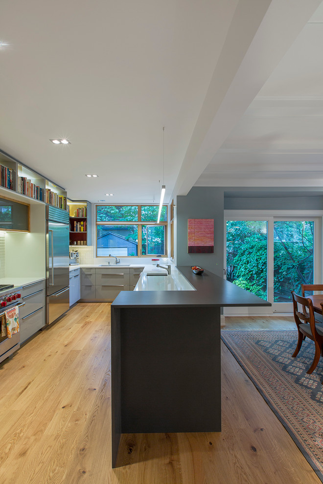 Eat-in kitchen - mid-sized contemporary u-shaped light wood floor eat-in kitchen idea in Toronto with an undermount sink, flat-panel cabinets, gray cabinets, quartz countertops, white backsplash, porcelain backsplash, stainless steel appliances and a peninsula