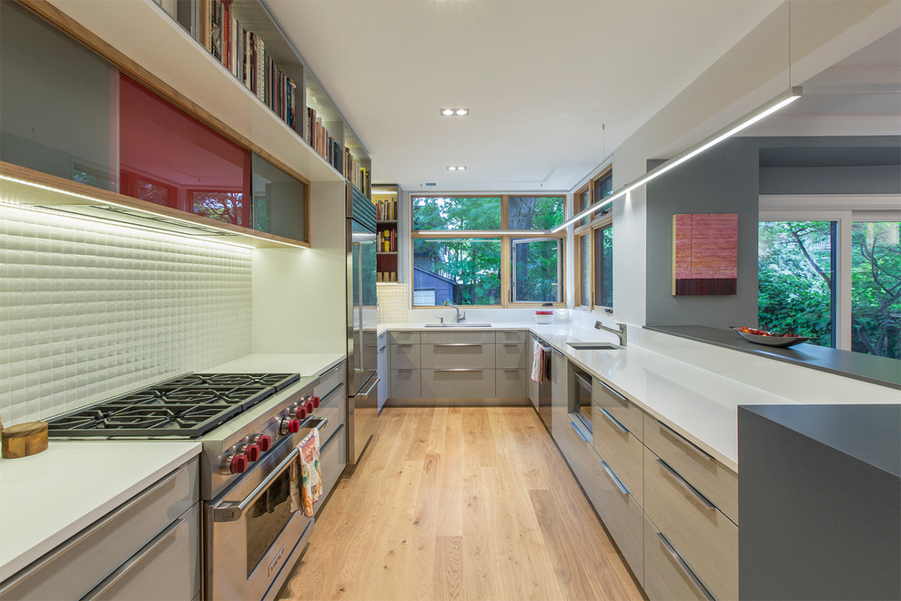 Kitchen - mid-sized contemporary u-shaped light wood floor kitchen idea in Toronto with an undermount sink, flat-panel cabinets, gray cabinets, quartz countertops, white backsplash, porcelain backsplash, stainless steel appliances and a peninsula