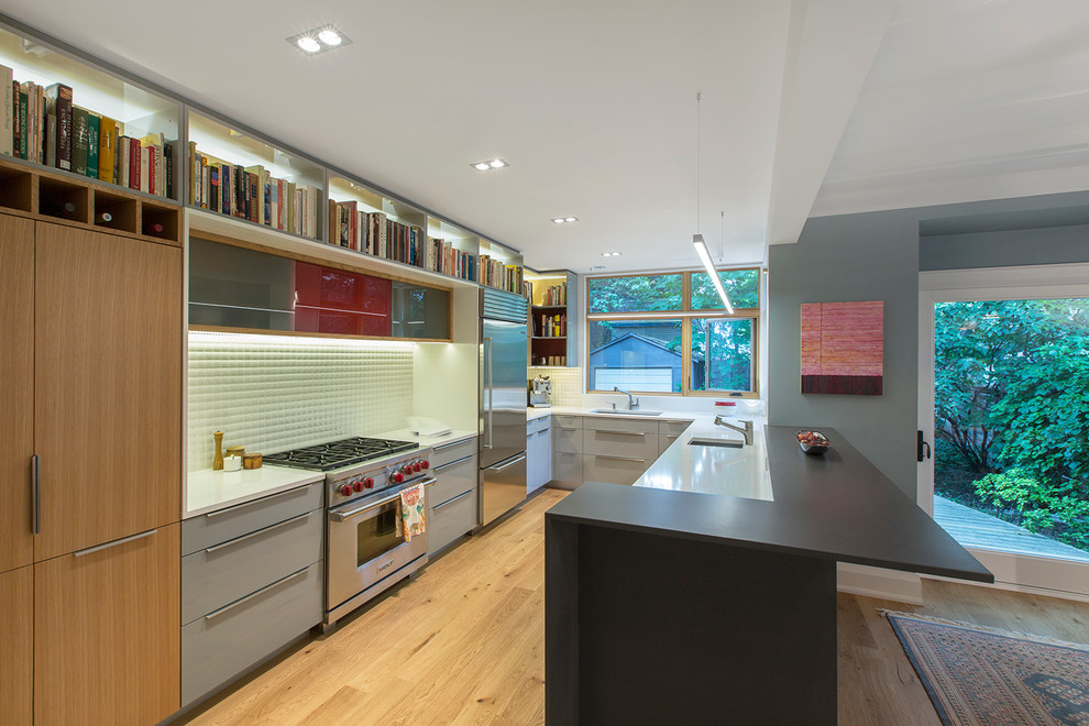 Example of a mid-sized trendy u-shaped light wood floor eat-in kitchen design in Toronto with an undermount sink, flat-panel cabinets, gray cabinets, quartz countertops, white backsplash, porcelain backsplash, stainless steel appliances and a peninsula