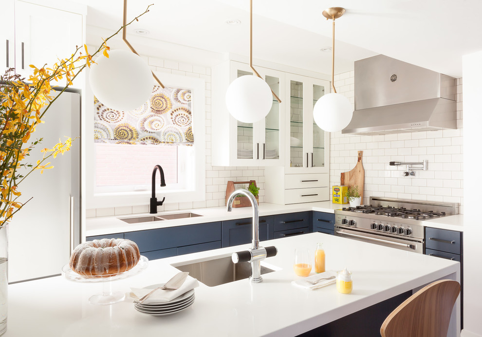 Transitional l-shaped kitchen photo in Toronto with an undermount sink, shaker cabinets, blue cabinets, white backsplash, subway tile backsplash, stainless steel appliances and an island