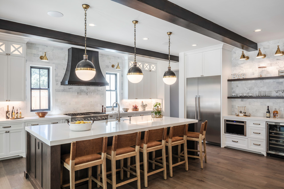 Example of a large transitional l-shaped medium tone wood floor and brown floor open concept kitchen design in San Francisco with a farmhouse sink, shaker cabinets, white cabinets, quartz countertops, gray backsplash, marble backsplash, stainless steel appliances, an island and white countertops