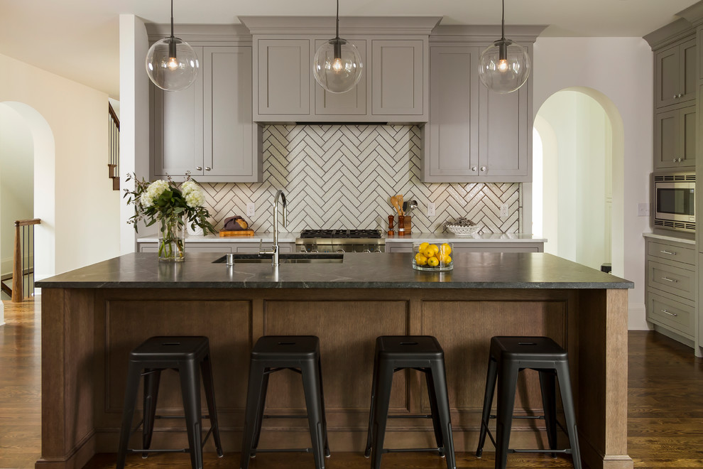 Inspiration for a large transitional dark wood floor and brown floor kitchen remodel in Minneapolis with an undermount sink, shaker cabinets, an island, gray cabinets, white backsplash, stainless steel appliances and granite countertops