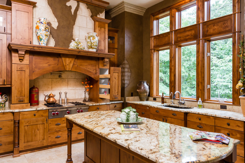 Example of a mountain style l-shaped kitchen design in Other with an undermount sink, shaker cabinets, medium tone wood cabinets, beige backsplash, stainless steel appliances and an island