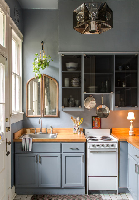 Kitchen - small traditional l-shaped kitchen idea in New Orleans with a drop-in sink, shaker cabinets, gray cabinets, wood countertops, white appliances and a peninsula