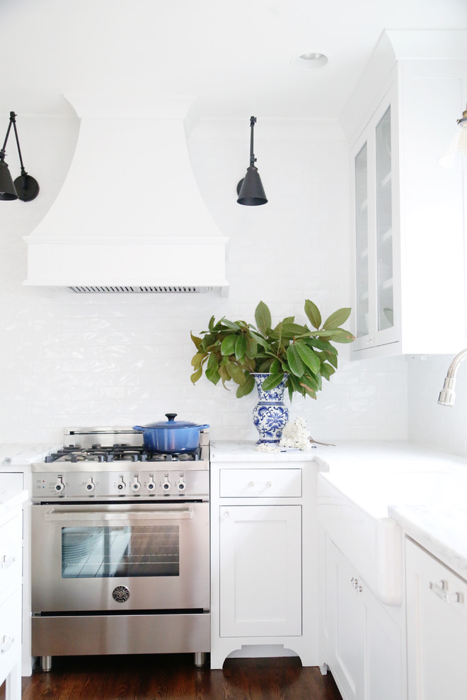 Inspiration for a mid-sized transitional u-shaped medium tone wood floor and brown floor eat-in kitchen remodel in Other with a farmhouse sink, glass-front cabinets, white cabinets, marble countertops, white backsplash, subway tile backsplash, stainless steel appliances and an island