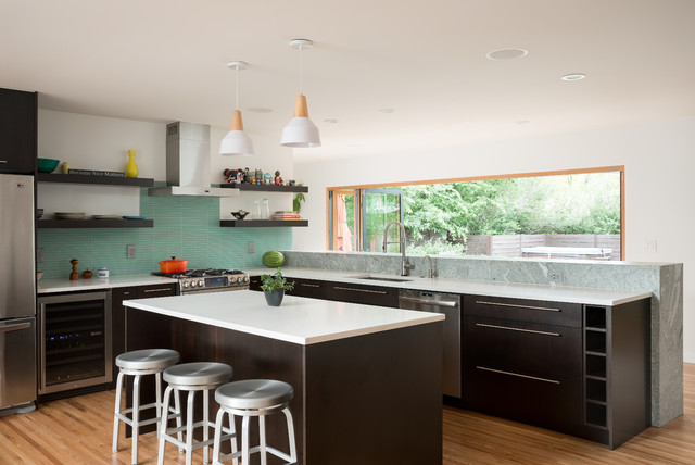 Trendy l-shaped light wood floor kitchen photo in Denver with an undermount sink, solid surface countertops, stainless steel appliances, an island, flat-panel cabinets, dark wood cabinets, blue backsplash and matchstick tile backsplash