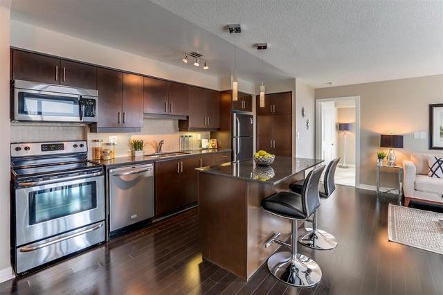 Imagen de cocina lineal, contemporánea, abierta, con fregadero de doble seno, salpicadero de azulejos de cerámica, electrodomésticos de acero inoxidable, suelo de madera oscura y una isla