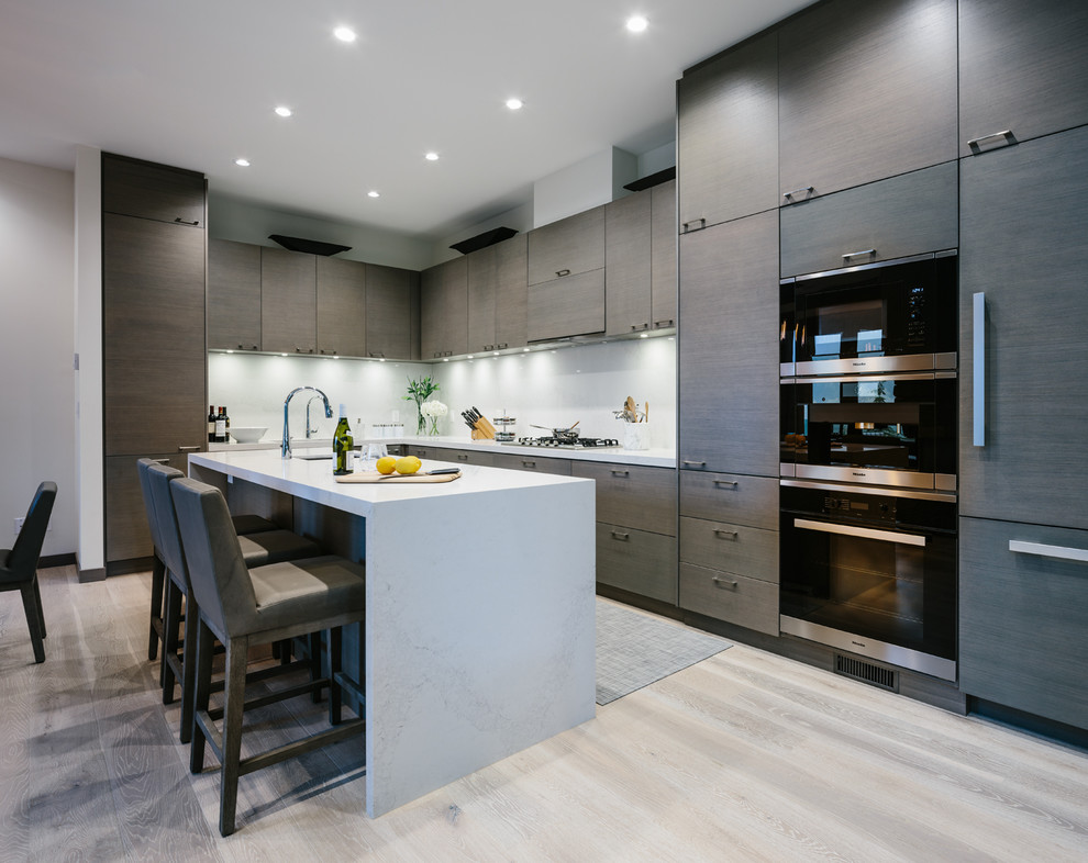 Large trendy l-shaped medium tone wood floor and gray floor eat-in kitchen photo in Vancouver with an undermount sink, flat-panel cabinets, dark wood cabinets, quartzite countertops, white backsplash, stone slab backsplash, paneled appliances and an island
