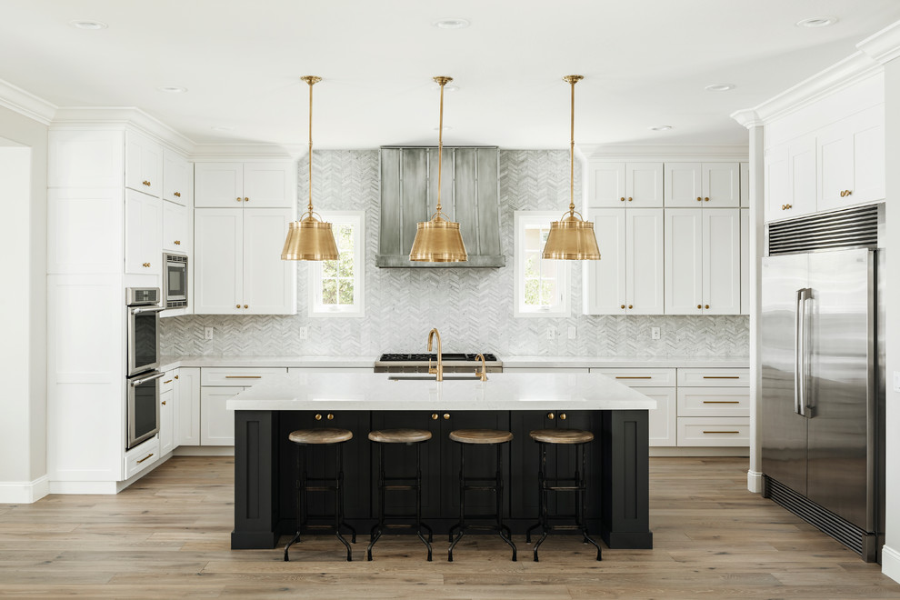 Large transitional galley light wood floor and beige floor open concept kitchen photo in Phoenix with an undermount sink, shaker cabinets, white cabinets, quartz countertops, gray backsplash, marble backsplash, stainless steel appliances, an island and white countertops