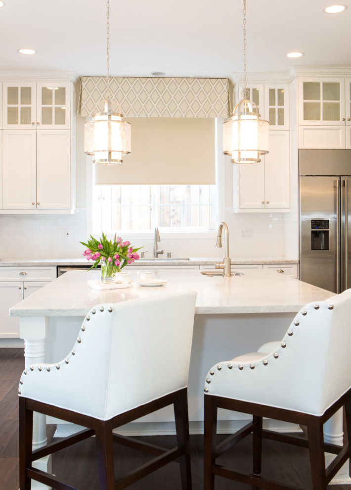 Example of a mid-sized classic single-wall dark wood floor enclosed kitchen design in Los Angeles with an undermount sink, shaker cabinets, white cabinets, marble countertops, white backsplash, ceramic backsplash, stainless steel appliances and an island