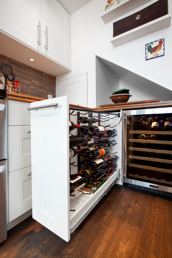 Inspiration for a transitional enclosed kitchen remodel in Vancouver with a farmhouse sink, shaker cabinets, white cabinets, wood countertops, brown backsplash, matchstick tile backsplash and stainless steel appliances