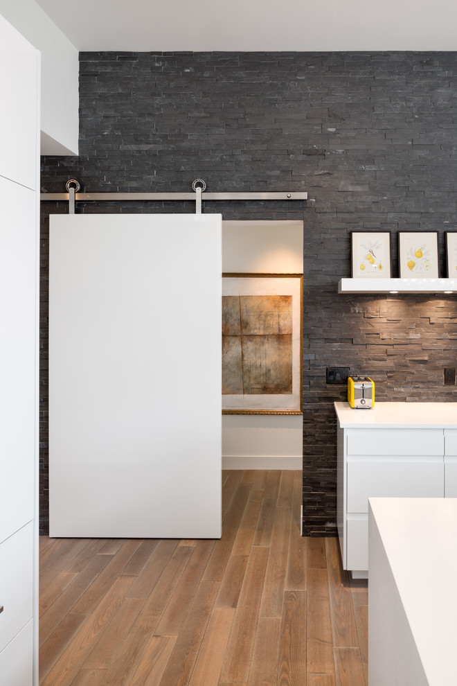Inspiration for a contemporary kitchen remodel in Portland with flat-panel cabinets, white cabinets, gray backsplash and stone tile backsplash