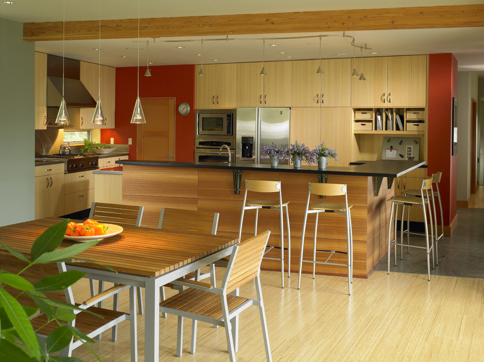 Trendy eat-in kitchen photo in Seattle with stainless steel appliances, flat-panel cabinets and light wood cabinets