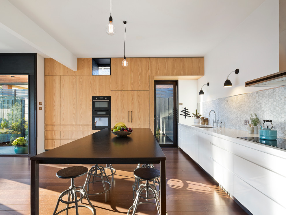 This is an example of a contemporary kitchen in Melbourne with an undermount sink, flat-panel cabinets, white cabinets, grey splashback, medium hardwood floors and an island.