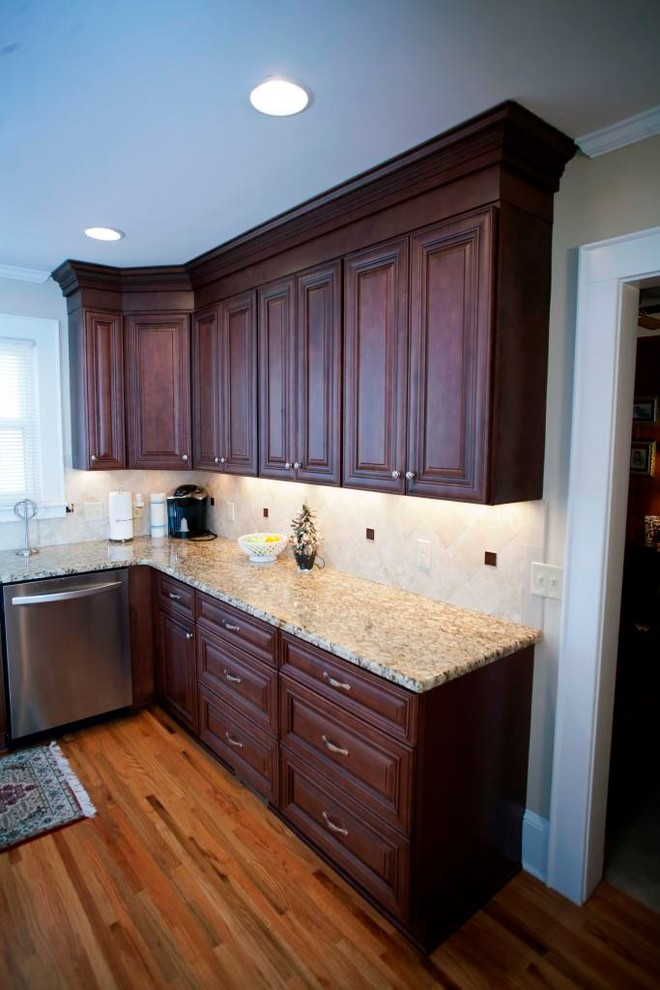 Example of a transitional u-shaped eat-in kitchen design in Charlotte with an undermount sink, raised-panel cabinets, dark wood cabinets, granite countertops, beige backsplash, subway tile backsplash and stainless steel appliances