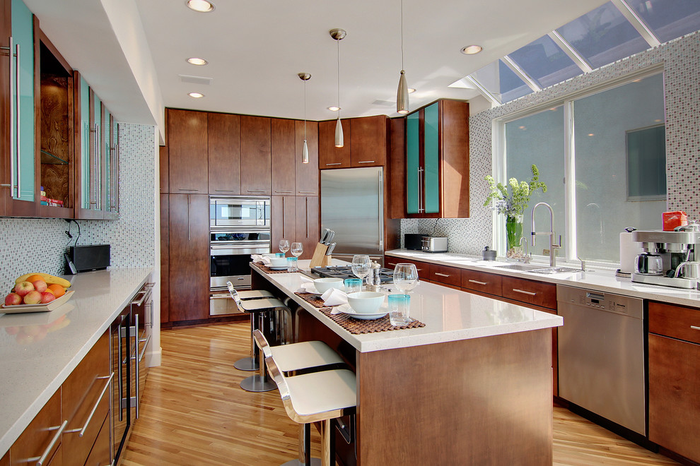 Inspiration for a contemporary kitchen remodel in Los Angeles with mosaic tile backsplash, stainless steel appliances, multicolored backsplash, flat-panel cabinets and dark wood cabinets