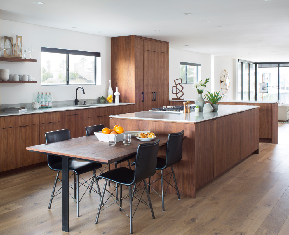 Open concept kitchen - contemporary u-shaped medium tone wood floor and brown floor open concept kitchen idea in Denver with flat-panel cabinets, medium tone wood cabinets, an island, an undermount sink, white backsplash, paneled appliances and gray countertops