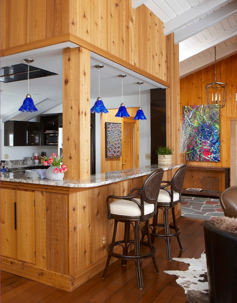 Inspiration for a mid-sized craftsman l-shaped medium tone wood floor and beige floor eat-in kitchen remodel in New York with flat-panel cabinets, black cabinets, granite countertops, stainless steel appliances and a peninsula