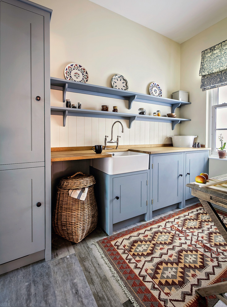 Country dark wood floor kitchen photo in London with a farmhouse sink, shaker cabinets, blue cabinets, wood countertops and paneled appliances