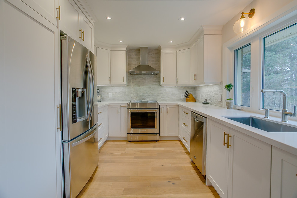 Example of a mid-sized transitional u-shaped medium tone wood floor eat-in kitchen design in Toronto with an undermount sink, shaker cabinets, white cabinets, quartz countertops, multicolored backsplash, porcelain backsplash, stainless steel appliances, a peninsula and white countertops