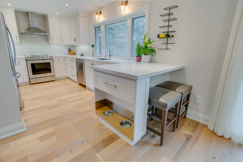 Inspiration for a huge transitional medium tone wood floor eat-in kitchen remodel in Toronto with an undermount sink, shaker cabinets, white cabinets, quartz countertops, multicolored backsplash, porcelain backsplash, stainless steel appliances, a peninsula and white countertops