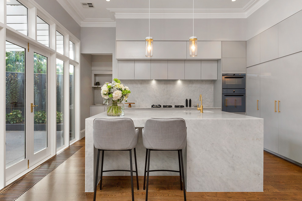 Kitchen - contemporary l-shaped medium tone wood floor and brown floor kitchen idea in Melbourne with an undermount sink, flat-panel cabinets, gray cabinets, white backsplash, an island, marble backsplash and black appliances