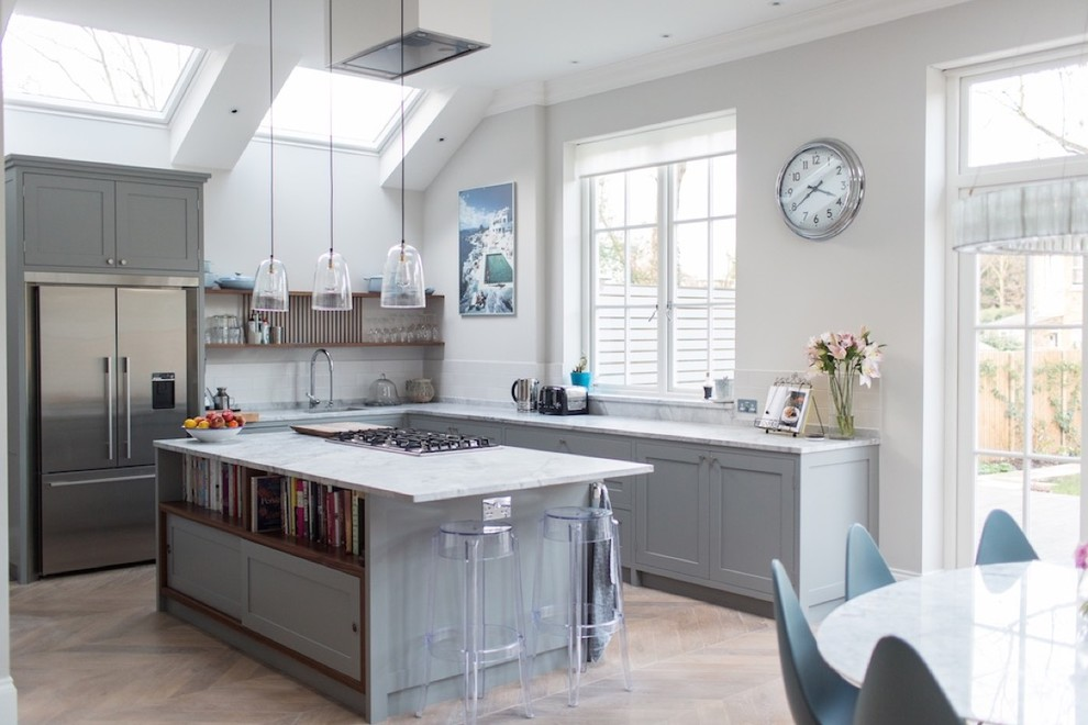 Transitional l-shaped light wood floor eat-in kitchen photo in London with shaker cabinets, gray cabinets, white backsplash, stainless steel appliances and an island