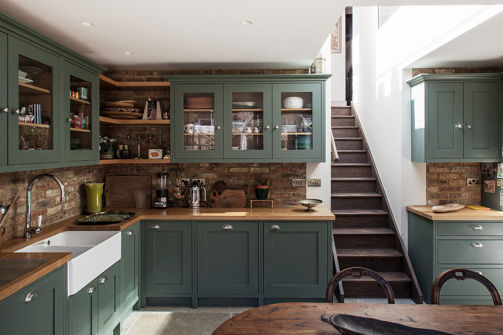 Eat-in kitchen - transitional l-shaped eat-in kitchen idea in London with glass-front cabinets, green cabinets, wood countertops, no island and a farmhouse sink