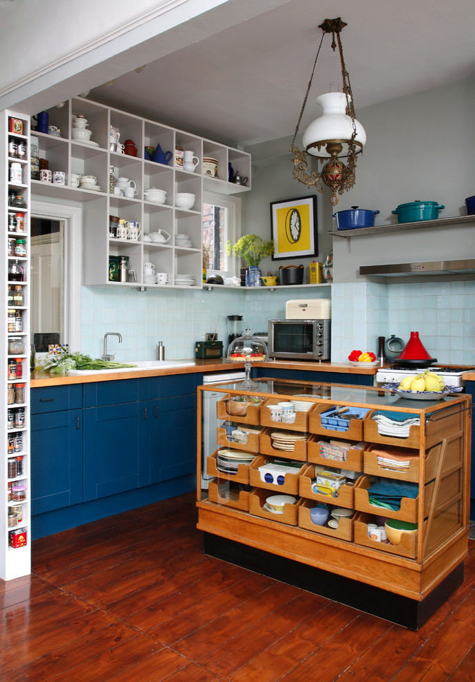 Eclectic l-shaped dark wood floor kitchen photo in London with a drop-in sink, shaker cabinets, blue cabinets, wood countertops, blue backsplash, ceramic backsplash and an island