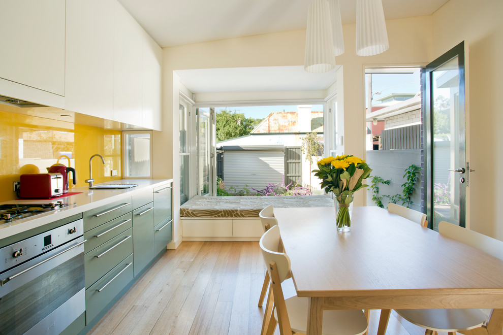 Inspiration for a small contemporary single-wall light wood floor eat-in kitchen remodel in Sydney with flat-panel cabinets, stainless steel appliances, yellow backsplash, glass sheet backsplash, green cabinets, a single-bowl sink and no island