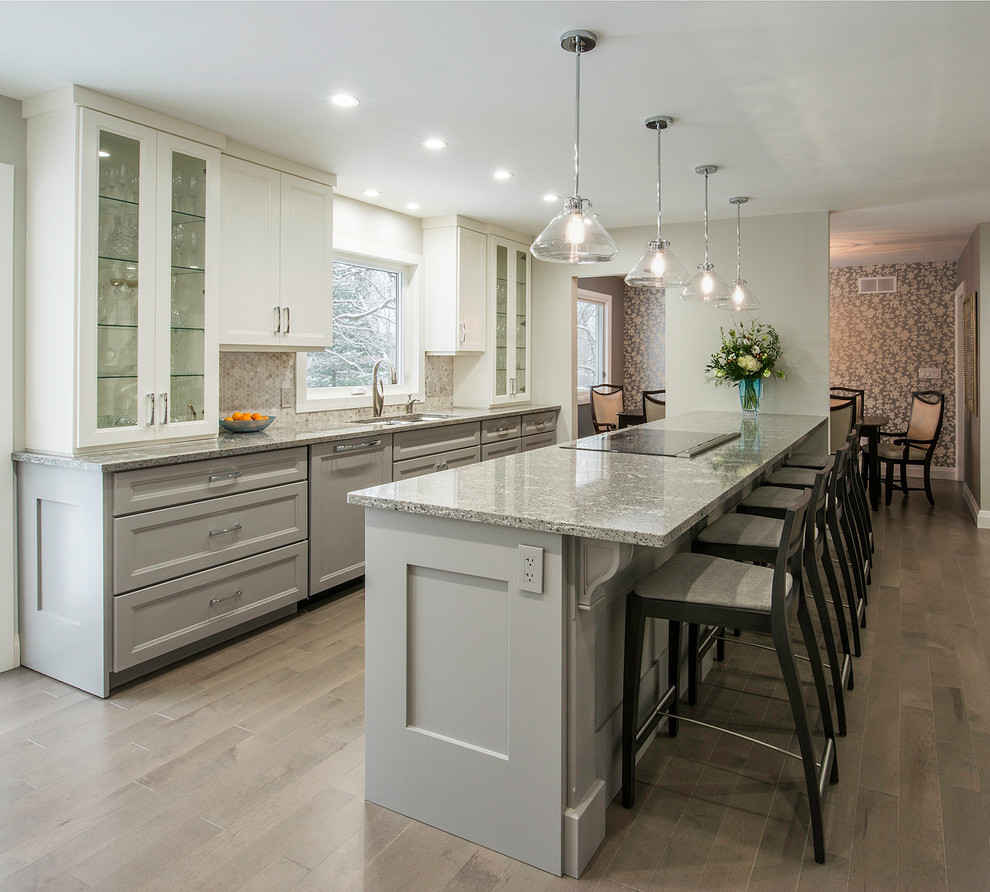 Mid-sized transitional medium tone wood floor open concept kitchen photo in Toronto with an undermount sink, gray cabinets, quartzite countertops, gray backsplash, mosaic tile backsplash, paneled appliances, a peninsula and shaker cabinets
