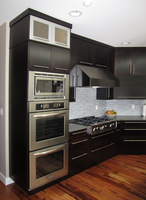 View of the double wall ovens, built-in microwave, gas cooktop, and hood..
