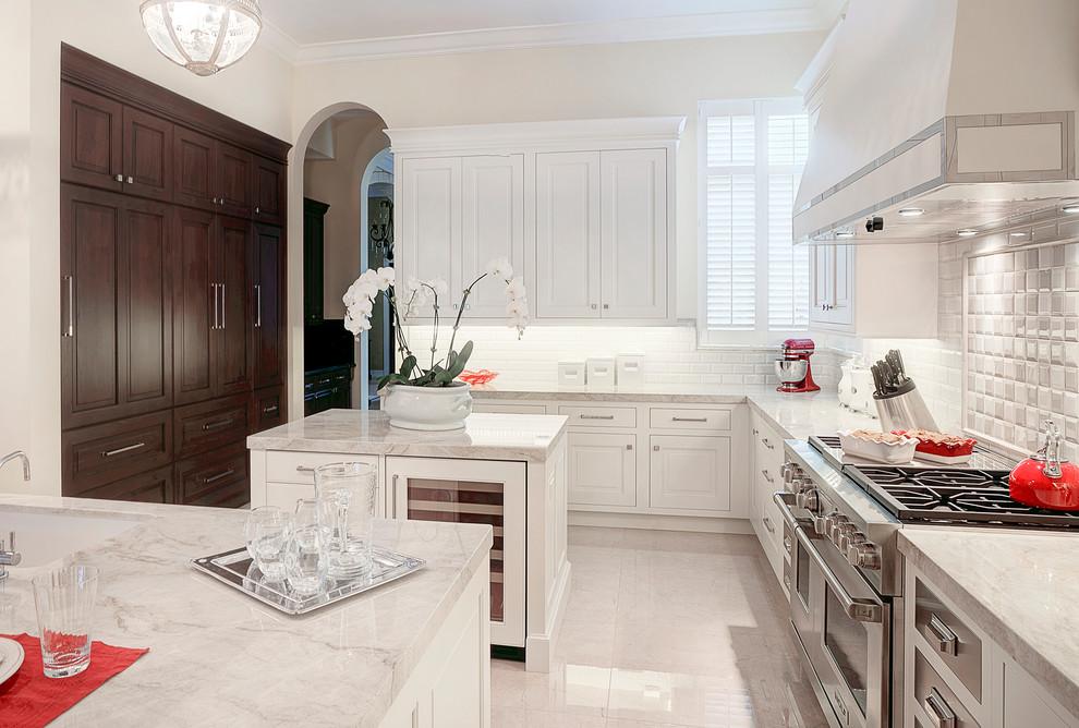 Kitchen - large traditional porcelain tile kitchen idea in Miami with a single-bowl sink, white cabinets, quartzite countertops, white backsplash, subway tile backsplash, paneled appliances, two islands and raised-panel cabinets
