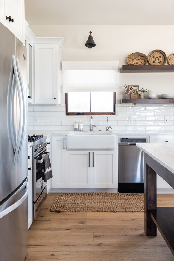 Example of a mid-sized cottage l-shaped light wood floor and brown floor open concept kitchen design in San Luis Obispo with a farmhouse sink, shaker cabinets, white cabinets, marble countertops, white backsplash, subway tile backsplash, stainless steel appliances, an island and white countertops