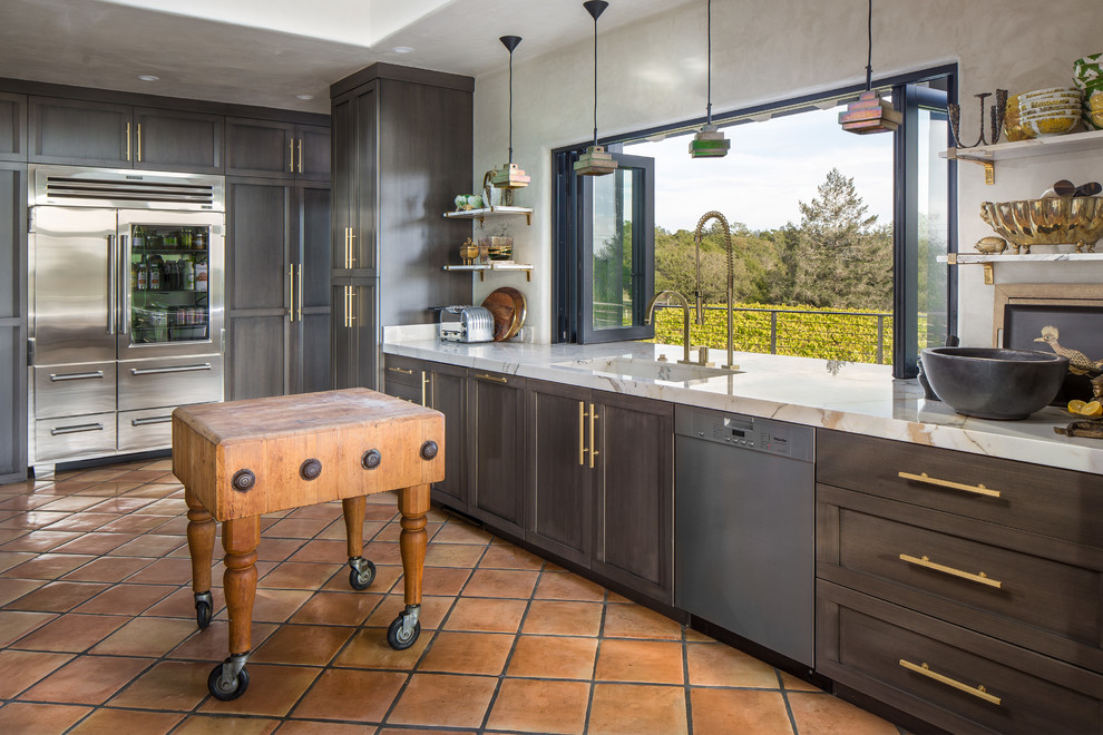Example of a large eclectic terra-cotta tile eat-in kitchen design in San Francisco with an integrated sink, gray cabinets, marble countertops, stainless steel appliances, an island and shaker cabinets