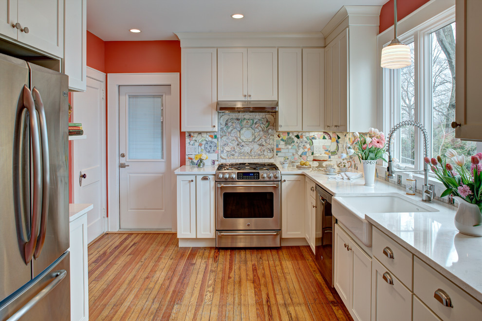 Inspiration for a mid-sized eclectic medium tone wood floor enclosed kitchen remodel in New York with a farmhouse sink, shaker cabinets, white cabinets, quartz countertops, multicolored backsplash, stainless steel appliances and no island