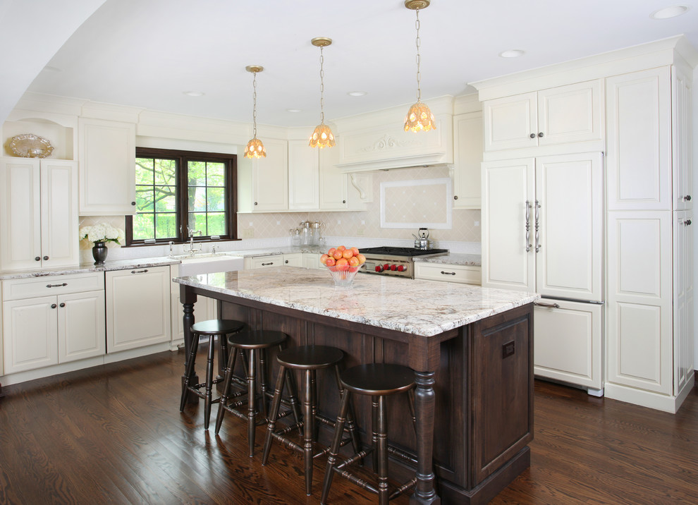 Kitchen - large traditional l-shaped dark wood floor kitchen idea in Chicago with raised-panel cabinets, white cabinets, beige backsplash, paneled appliances, an island, a farmhouse sink, granite countertops and ceramic backsplash