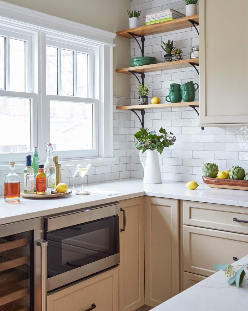 Eat-in kitchen - traditional u-shaped medium tone wood floor eat-in kitchen idea in Chicago with a farmhouse sink, shaker cabinets, beige cabinets, quartzite countertops, white backsplash, porcelain backsplash, stainless steel appliances, an island and beige countertops