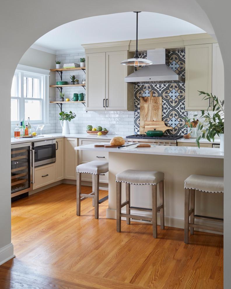 Eat-in kitchen - large traditional u-shaped medium tone wood floor and brown floor eat-in kitchen idea in Chicago with a farmhouse sink, shaker cabinets, beige cabinets, quartzite countertops, multicolored backsplash, porcelain backsplash, stainless steel appliances, an island and beige countertops