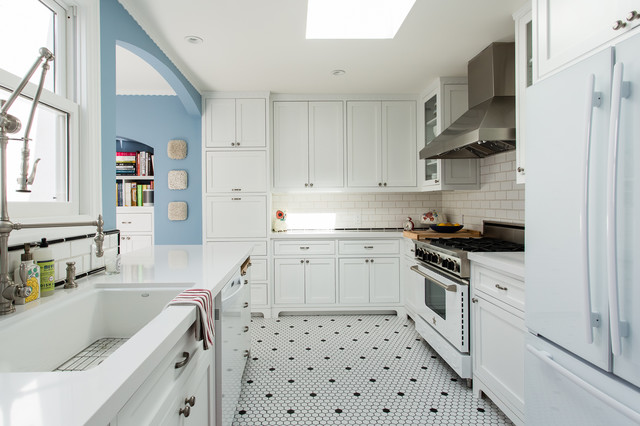 Large trendy l-shaped porcelain floor and white floor eat-in kitchen photo in San Francisco with an undermount sink, shaker cabinets, white cabinets, solid surface countertops, white backsplash, subway tile backsplash, stainless steel appliances and an island