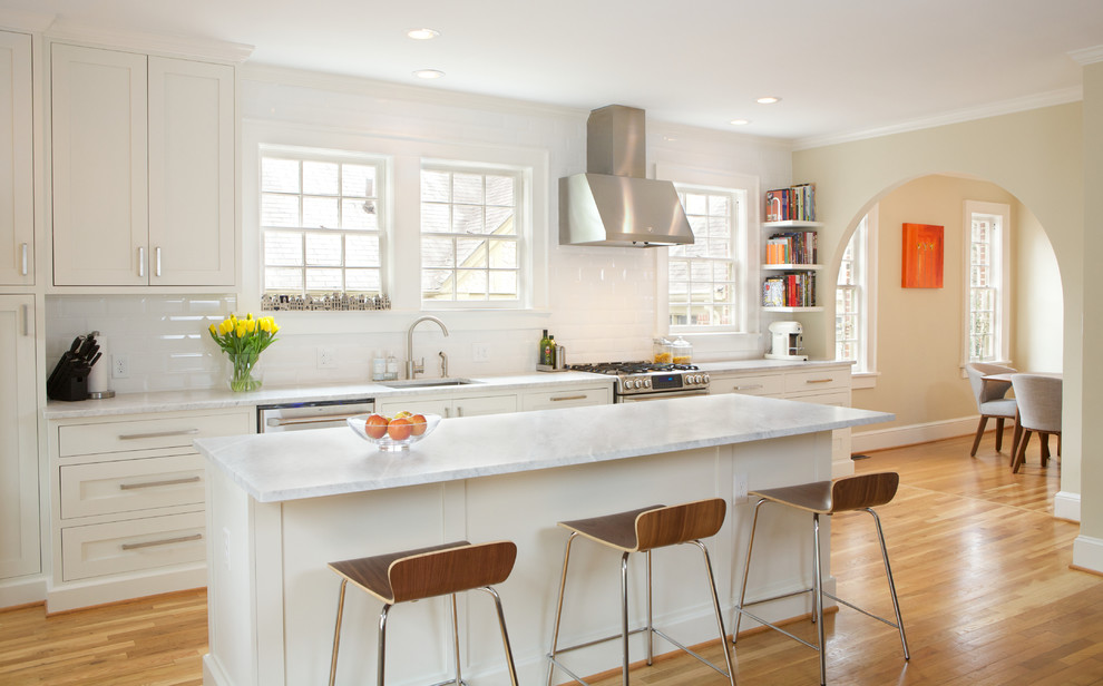 Eat-in kitchen - mid-sized transitional single-wall light wood floor eat-in kitchen idea in Atlanta with an undermount sink, shaker cabinets, white cabinets, marble countertops, white backsplash, ceramic backsplash, stainless steel appliances and an island