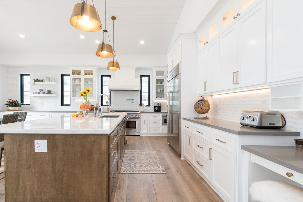 Inspiration for a transitional l-shaped medium tone wood floor and brown floor kitchen remodel in Orange County with an undermount sink, shaker cabinets, white cabinets, white backsplash, stainless steel appliances, an island and gray countertops