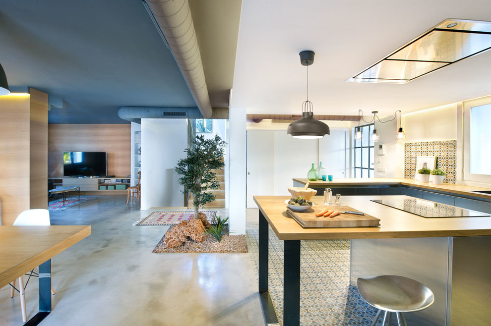 Inspiration for a large industrial u-shaped eat-in kitchen remodel in Madrid with flat-panel cabinets, stainless steel cabinets, wood countertops, multicolored backsplash, ceramic backsplash, stainless steel appliances and an island