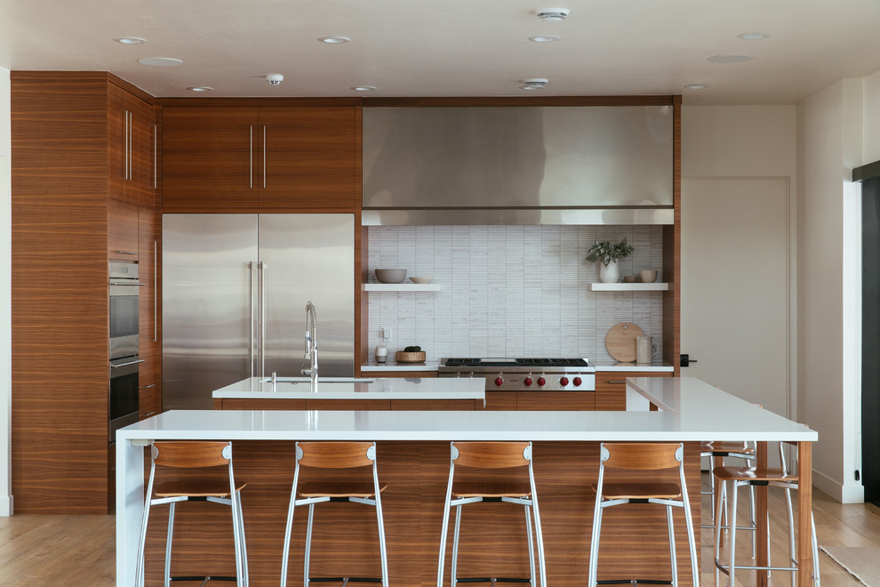 Kitchen - contemporary l-shaped medium tone wood floor and brown floor kitchen idea in Salt Lake City with an undermount sink, flat-panel cabinets, medium tone wood cabinets, white backsplash, stainless steel appliances, two islands and white countertops