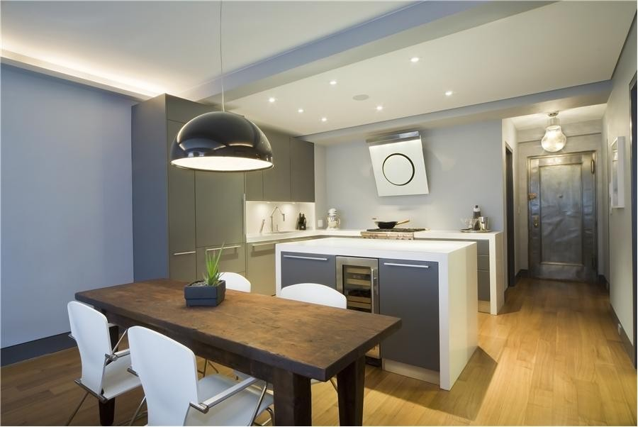 Mid-sized minimalist l-shaped light wood floor and brown floor eat-in kitchen photo in New York with an undermount sink, flat-panel cabinets, gray cabinets, solid surface countertops, white backsplash, stainless steel appliances and an island