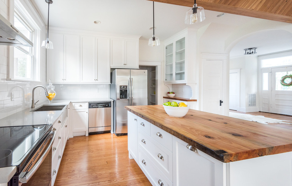 Eat-in kitchen - large farmhouse l-shaped medium tone wood floor eat-in kitchen idea in Richmond with a farmhouse sink, shaker cabinets, white cabinets, wood countertops, white backsplash, subway tile backsplash, stainless steel appliances and an island