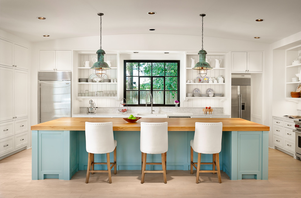 Inspiration for a large beach style u-shaped light wood floor kitchen remodel in Houston with an island, white cabinets, marble countertops, stainless steel appliances, open cabinets, a farmhouse sink, white backsplash and wood backsplash